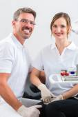 Dentists in their surgery or office with dental tools