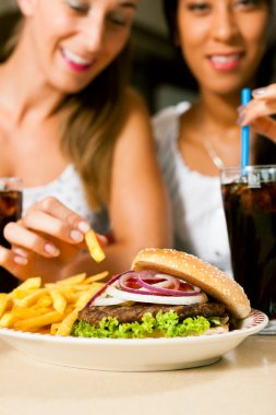 women eating hamburger and drinking soda