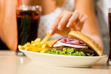 women eating hamburger and drinking soda