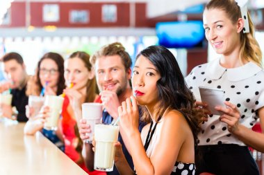 People in American diner with milk shakes