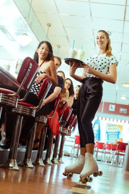 People in American diner with waitress