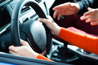 Driving School - Young woman steer a car with the steering wheel, maybe she has a driving test perhaps she exercises the parking stock vector