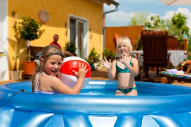 Children playing with ball in water pool