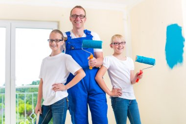 Father and Kids paint a wall in home