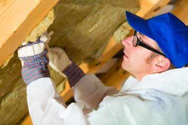 Worker setting thermal insulating material
