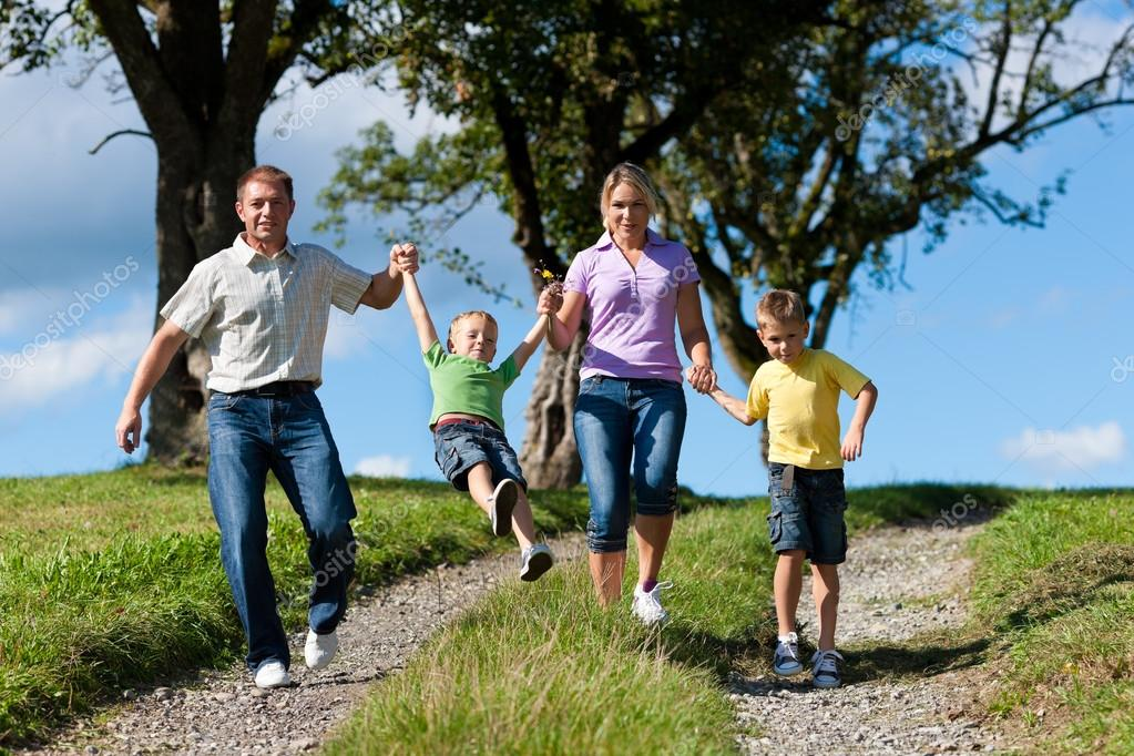 Family outdoors is running on a dirt path