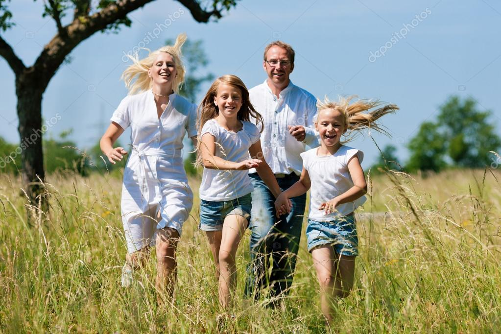 Family running in the meadow