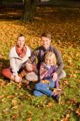 Šťastná rodina sedí venku na trávě na podzim