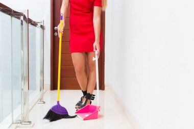 Woman cleaning up sweep floor with broom and shovel