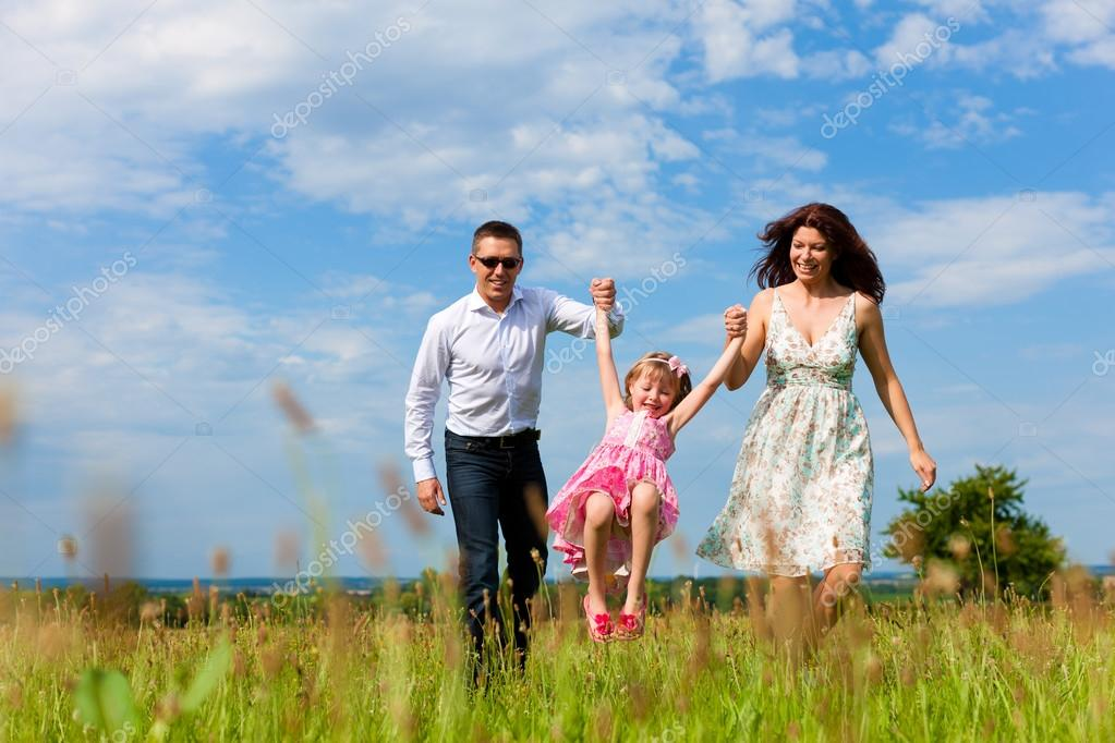 Happy family running on meadow in summer