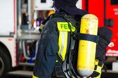 mladý hasič v uniformě před firetruck