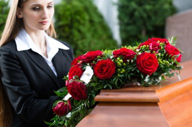 Mourning woman on funeral with red rose standing at casket or coffin stock vector
