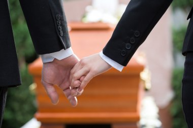 Religion, death and dolor - couple at funeral holding hands consoling each other in view of the loss stock vector