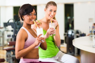 Women in the gym drinking a isotonic drink