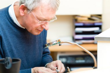 Acoustician working on a hearing aid