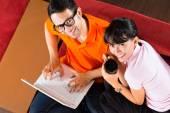 Asian pár a kanapén egy laptop