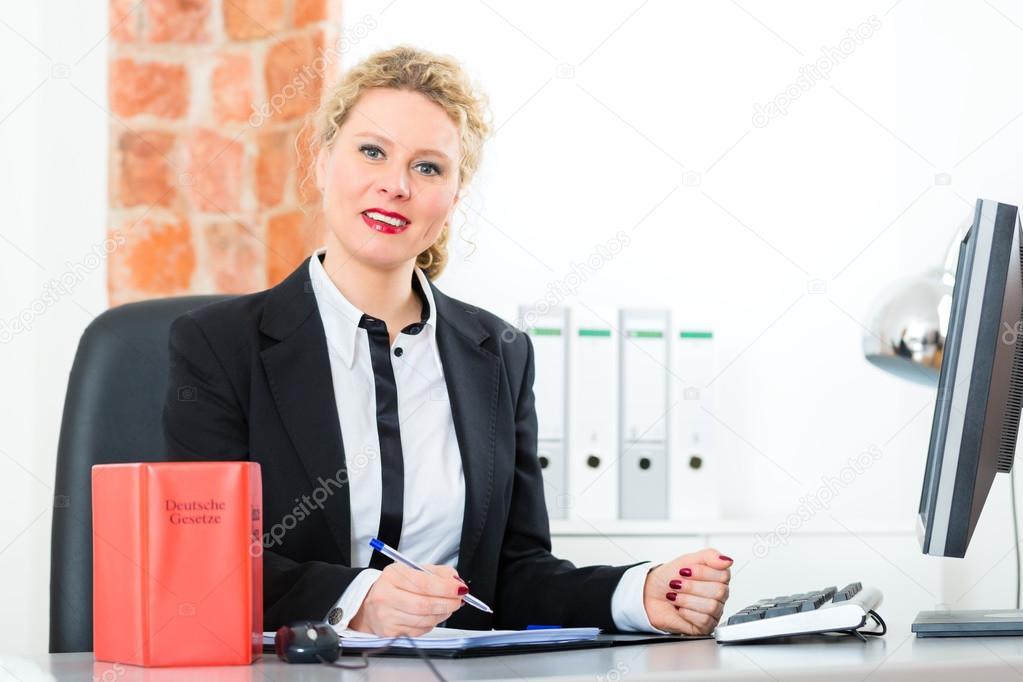 Scrivania Ufficio Avvocato : Avvocato in ufficio con il libro di legge lavorando sulla