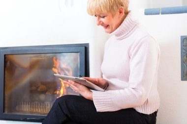 Female Senior at home in front of fireplace