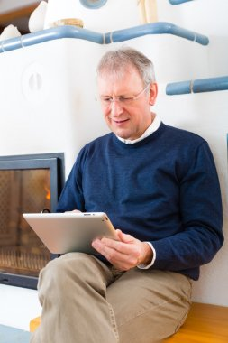 Senior at home in front of fireplace