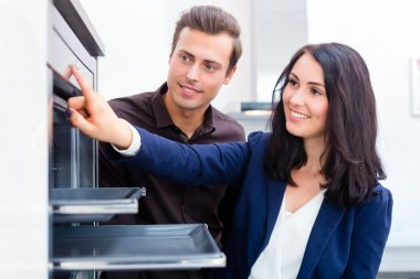 Couple buying domestic kitchen in furniture store