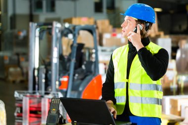 Worker with scanner and laptop at forwarding