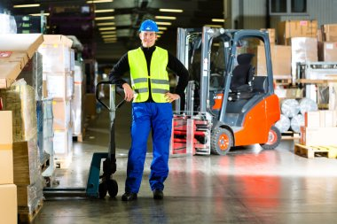 Warehouseman in protective vest holds a mover