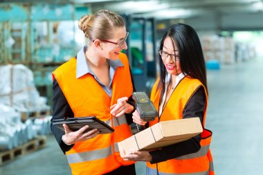 workers with package in warehouse of forwarding