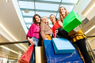 Four female friends with shopping bags having fun while shopping in a mall, stores in the background stock vector