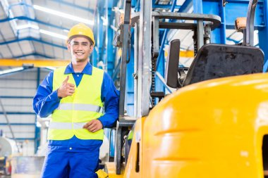 Forklift driver standing in manufacturing plant