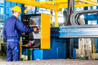 Worker in manufacturing plant at machine control panel