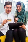 Asiatische muslimischen paar online-shopping auf Pad im Wohnzimmer