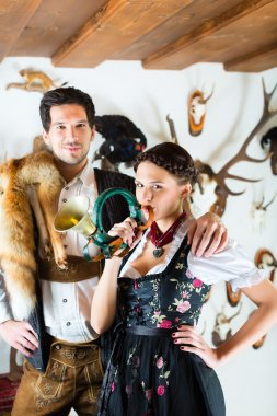 Hunter and woman in an alpine mountain hut with horn