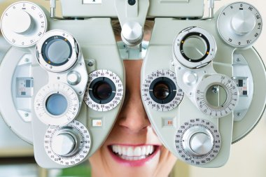 Young woman at phoropter for eye test