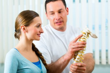 Physiotherapist in his practice, he explains a female patient