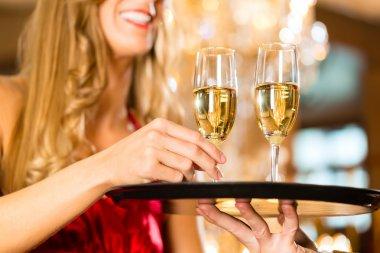 Waiter serves champagne glasses on tray in restaurant