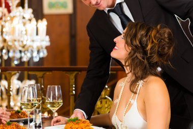 Beautiful woman and waiter in fine dining restaurant