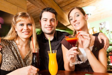 Young happy people drinking cocktails in bar or restaurant; presumably it is a little party stock vector