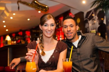 couple drinking cocktails in bar or restaurant