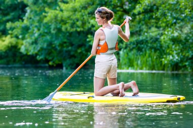 Woman with stand up paddle board sup on river