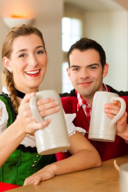 Young couple in traditional Bavarian Tracht in restaurant or pub