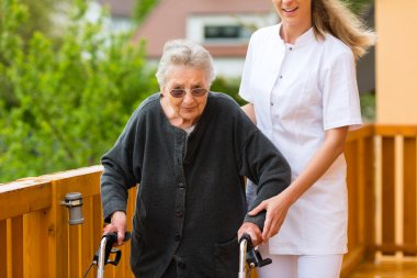 nurse and female senior with walking frame