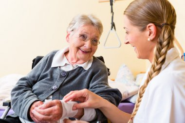 Nurse taking care of senior woman in retirement home