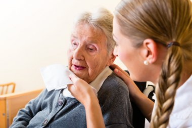 Nurse wiping mouth of senior woman in nursing home