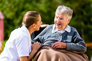 Nurse holding hands with senior woman in wheelchair