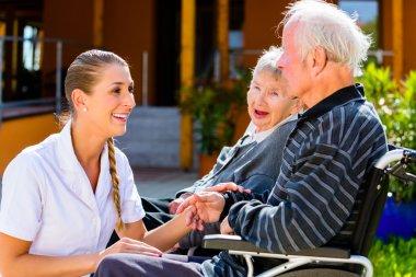 Seniors eating candy in garden of nursing home