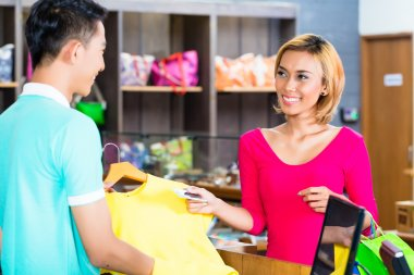Asian woman paying purchase in fashion store