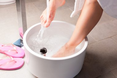 Woman having hydrotherapy water footbath
