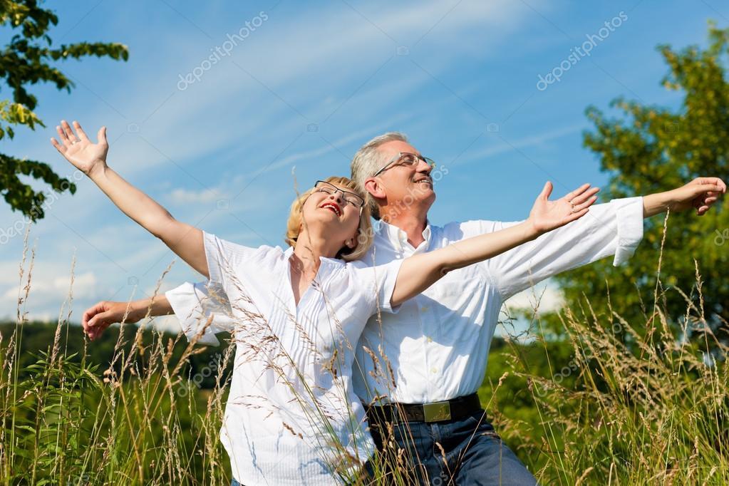 Happy senior couple having fun outdoors in summer