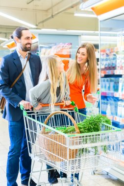 Family with shopping cart in supermarket store