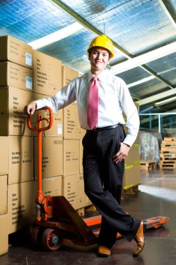 Young man in a suit standing besides boxes and packages in a warehouse stock vector